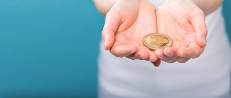 Woman holding a physical ripple cryptocurrency in her hand