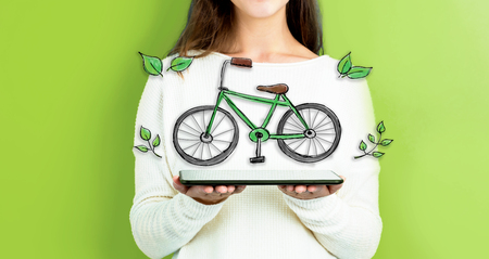 Eco Bicycle with woman holding a tablet computer Stock Photo