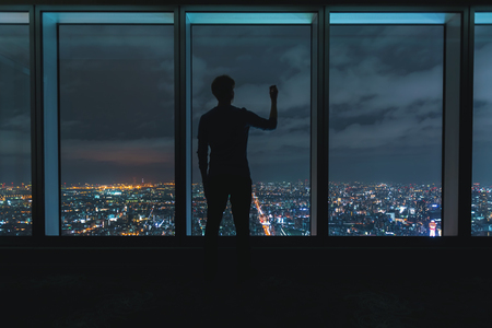 Man writing on large windows high above a sprawling city at night