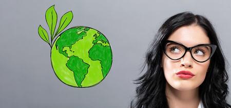 Green Earth with young businesswoman in a thoughtful face Stock Photo