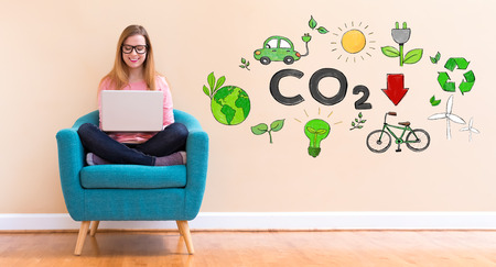 Reduce CO2 with young woman using her laptop in a chair Stock Photo