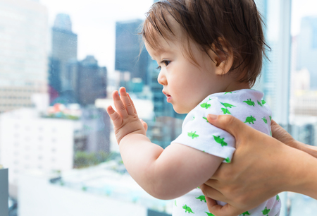 Toddler boy looking out at Downtown Los Angeles from a glass balcony Stok Fotoğraf