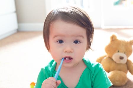 One year old toddler boy brushing his teeth