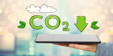 Reduce CO2 with man holding a tablet computer Foto de archivo - 97778418