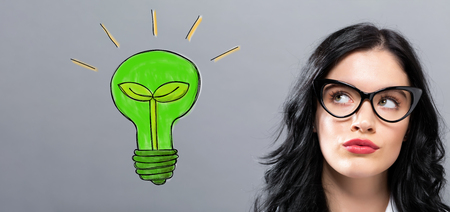Eco Light Bulb with young businesswoman in a thoughtful face