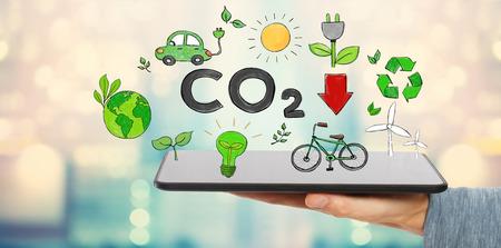 Verminder CO2 met de man die een tabletcomputer vasthoudt