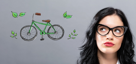 Eco Bicycle with young businesswoman in a thoughtful face Stock Photo