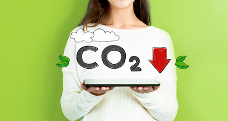 Reduce CO2 with woman holding a tablet computer Stok Fotoğraf