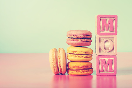 Macarons with MOM message on wooden blocks on pastel pink and blue background