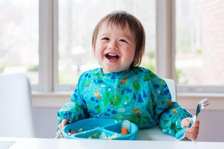 Gelukkige peuterjongen met een grote glimlach die voedsel eet