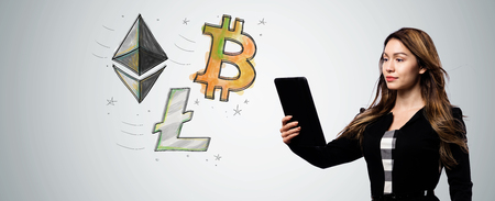 Bitcoin Ethereum and Litecoin with businesswoman holding a tablet computer