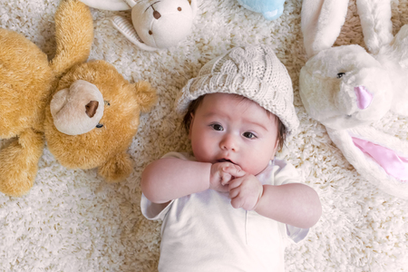 Baby boy with his stuffed animals on a white carpet