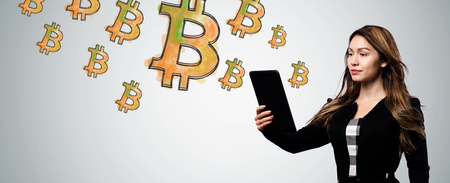 Bitcoin with businesswoman holding a tablet computer Stock Photo