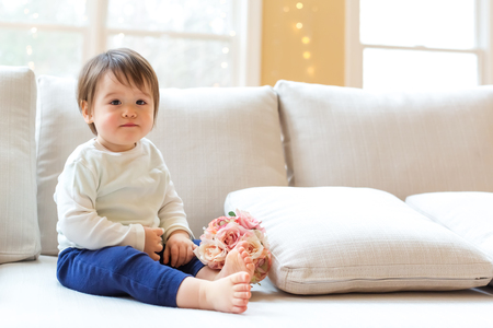 Toddler boy with spring flowers on a couch