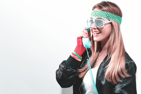 Woman in 1980s fashion with old fashioned phone on a white background Stockfoto