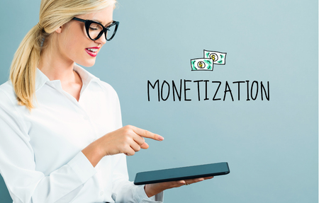 Monetization text with business woman using a tablet Stock Photo