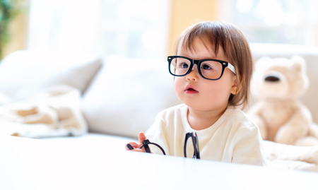One year old toddler boy with eyeglasses in a living room