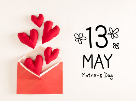 Mothers Day message with red heart cushions coming out of an envelope