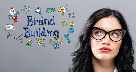 Brand Building with young businesswoman in a thoughtful face Stock Photo