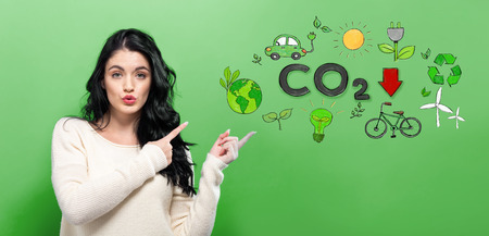 Reduce CO2 with young woman on a green background Stok Fotoğraf