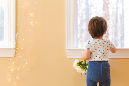 Toddler boy holding flowers in his house