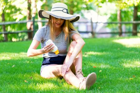 Jeune femme une bouteille d'écran solaire à l'extérieur un jour d'été