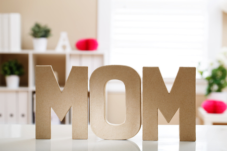 Mom letter blocks on a table in a room