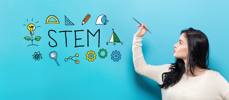 STEM with young woman holding a pen on a blue background Banque d'images - 98868070