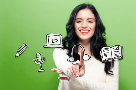 E-Learning with young woman pointing on a green background Stok Fotoğraf - 99308942