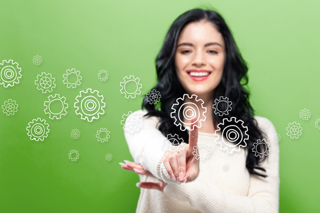 Gears with young woman pointing on a green background 写真素材