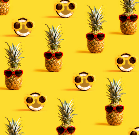 Series of pineapples and coconuts wearing sunglasses on a yellow background Stock Photo