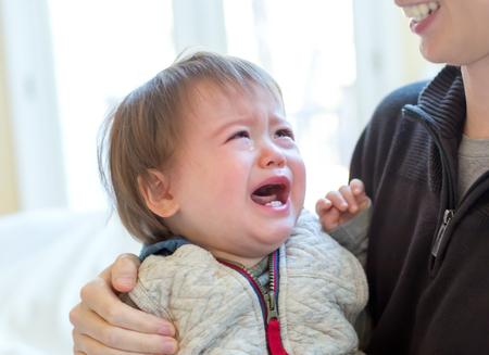 Upset toddler boy crying in his fathers arms