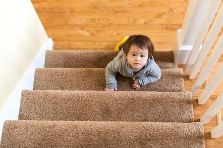 Toddler boy climbing a staircase in his house