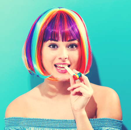 Party theme with a woman in a colorful wig on a blue background Stock Photo