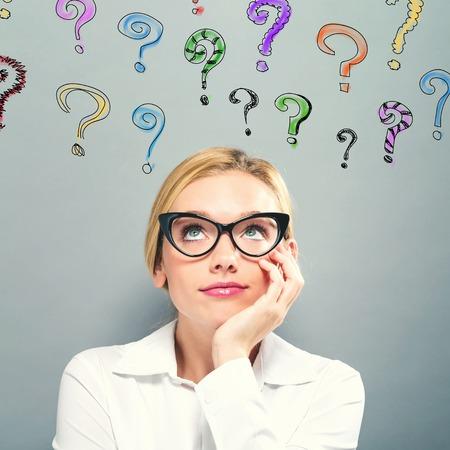 Signos de interrogación con mujer de negocios sobre un fondo gris Foto de archivo - 99716887