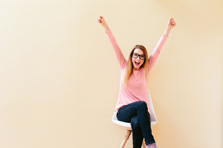 Happy young woman cheering with her arms in the air Stock fotó