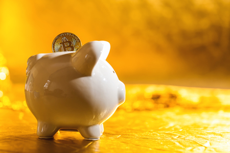 Bitcoin coin with piggy bank on a shiny golden background Фото со стока