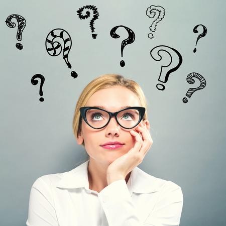 Punti interrogativi con donna d'affari su uno sfondo grigio Archivio Fotografico