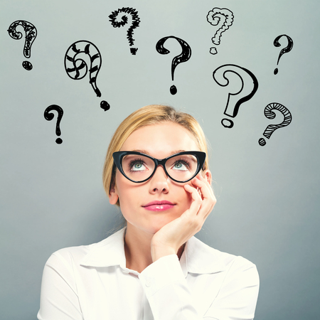 Question Marks with business woman on a gray background