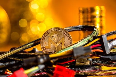 Monero cryptocurrency-muntstuk met computerdraden op een gouden achtergrond