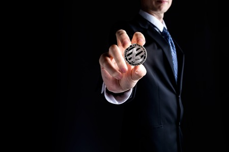 Litecoin cryptocurrency coin held out by a man in a suit