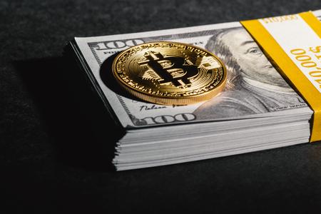 暗い背景に米ドル現金で暗号通貨コインをビットコイン