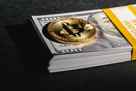 Bitcoin cryptocurrency coin with USD cash on a dark background 스톡 콘텐츠