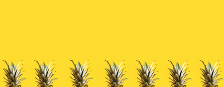 Series of pineapple tops on a yellow background
