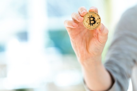 Bitcoin cryptocurrency coin held by a man in a bright room