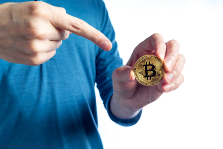 Bitcoin cryptocurrency coin held by a man on a white background Stock Photo