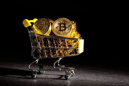Bitcoin cryptocurrency coins with shopping cart consumer spending theme Zdjęcie Seryjne
