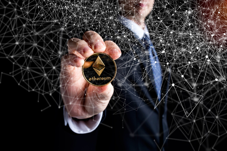Ethereum ether cryptocurrency coin held out by a man in a suit Zdjęcie Seryjne