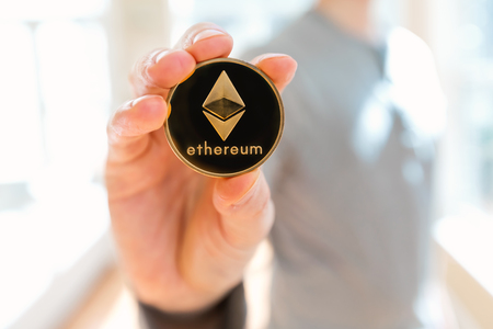 Ethereum cryptocurrency coin held by a man in a bright room