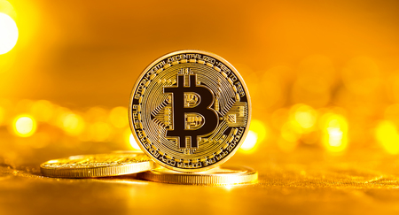 Bitcoin cryptocurrency coin on a bright gold background